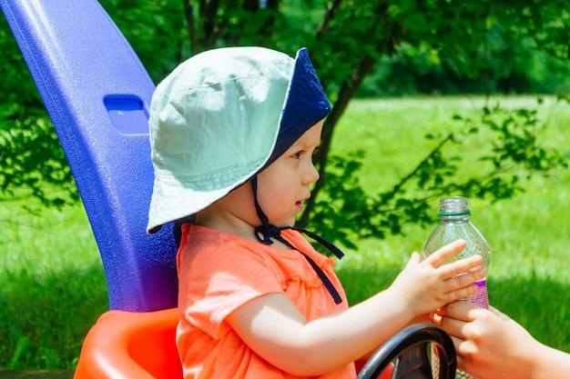 Mère attentionnée donne fille boire des bouteilles d'eau parc d'été