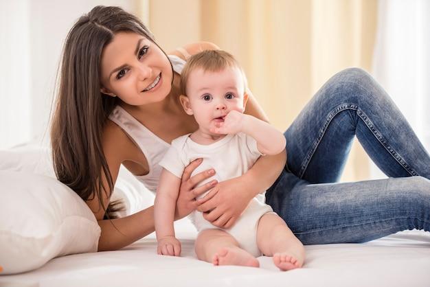 Mère avec bébé allongé sur le lit dans sa chambre.