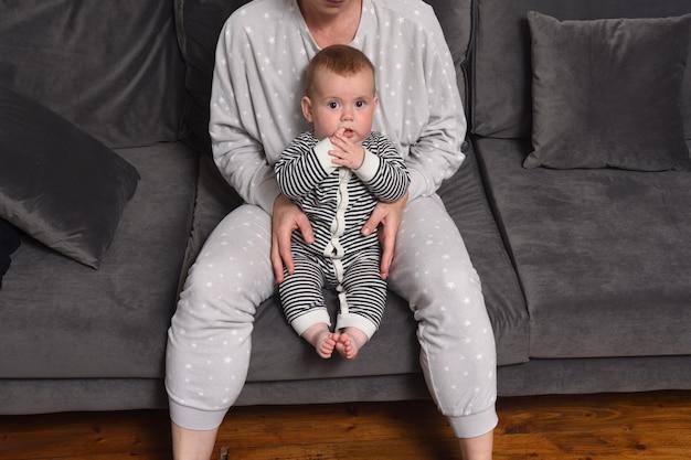 Mère et bébé assis ensemble sur le canapé