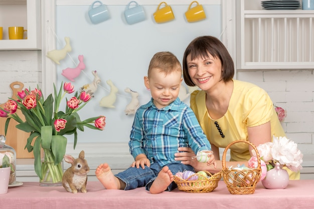 Mère et bébé dans la cuisine pastel décorée de pâques.