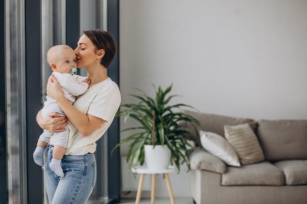 Mère avec bébé debout à la maison près de la fenêtre