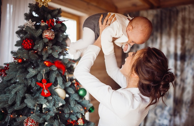 La mère avec bébé debout près de l'arbre de noël