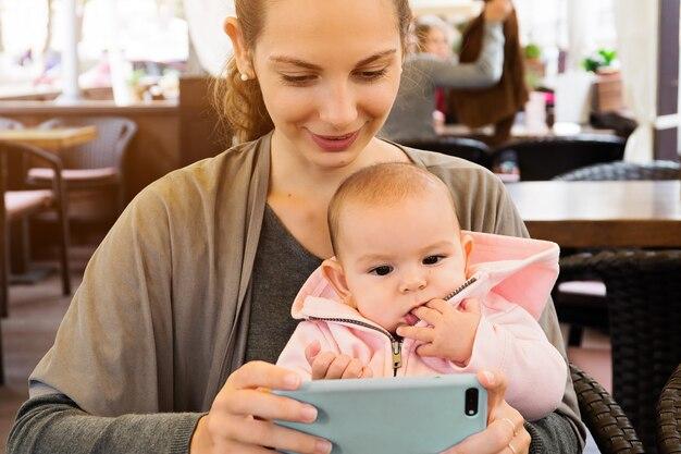 Mère et bébé dehors dans un restaurant regardant des cartons, faisant selfie