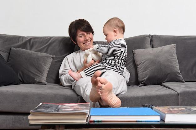Mère et bébé détendus et jouant sur le canapé