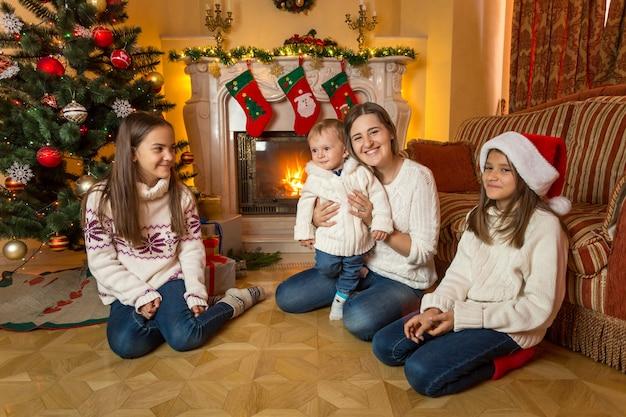 Mère, bébé et deux filles à l'étage à côté de la cheminée à noël