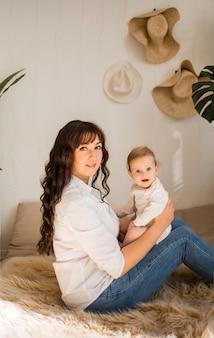 Mère et bébé fille s'asseoir sur le côté sur le canapé