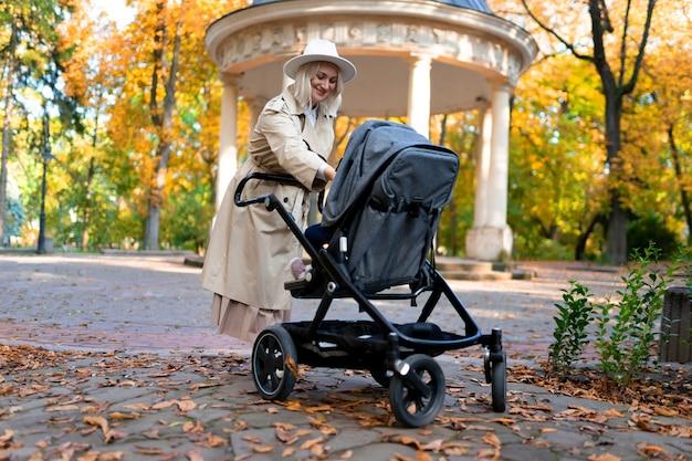 Mère avec bébé landau marchant dans le parc de l'automne