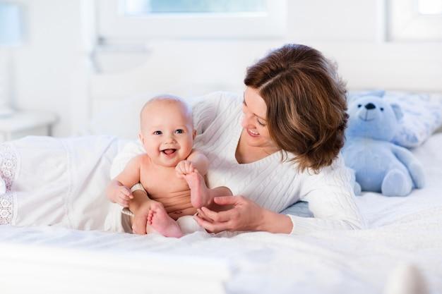 Mère et bébé sur un lit blanc