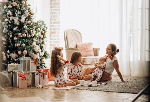 Une mère avec un bébé sur les mains est assise sur le tapis avec ses deux filles en pyjama en train de manger des biscuits au cacao avec des guimauves près de l'arbre du nouvel an dans la chambre confortable .
