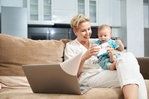 Mère avec bébé sur les mains ouvrant une boîte cadeau à la maison