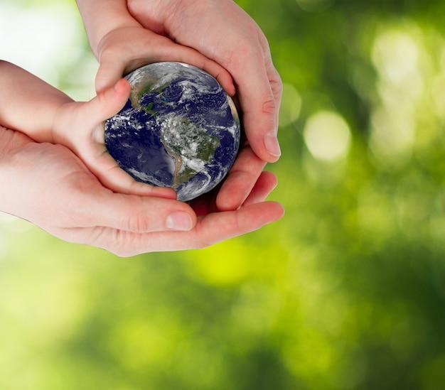 Mère et bébé mains tenant et protégeant la terre sur fond de nature défocalisé bokeh vert. éléments de cette image fournis par la nasa