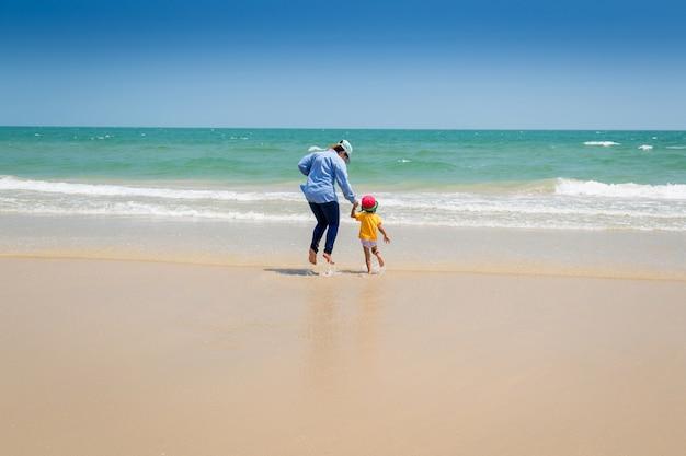 Mère et bébé marchant vers la mer