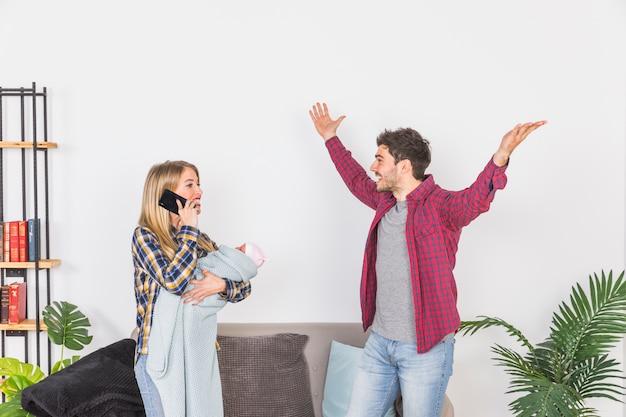 Mère avec bébé parle au téléphone près de père heureux