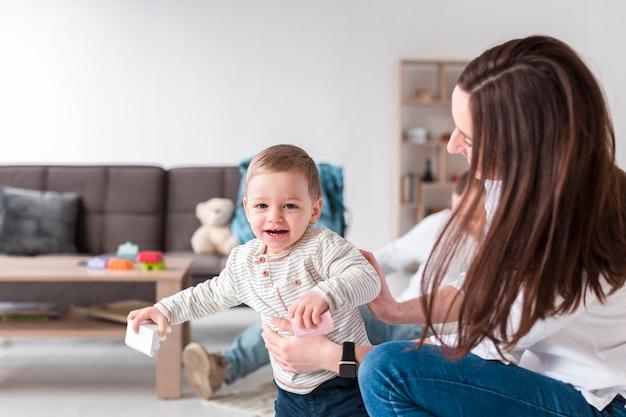 Mère avec bébé souriant à la maison