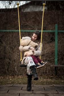 Mère bénéficiant d'une balançoire dans un parc avec son tout-petit sur ses genoux