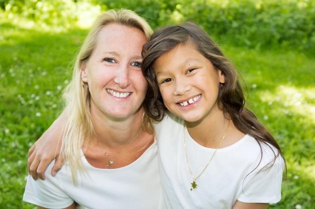 Mère blonde et sa fille mixte américaine assis dans l'herbe