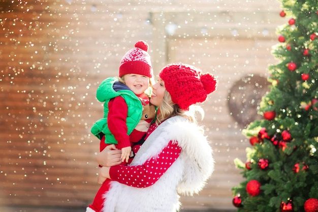 Une mère blonde tient son fils qui rit dans un pull de noël et un chapeau rouge sous la neige sur le fond d'un arbre de noël. photo de haute qualité