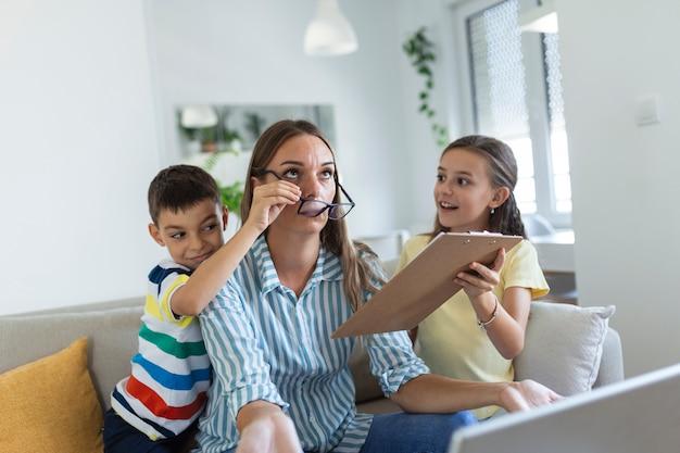 Mère bouleversée ayant un problème avec une fille et un fils vilains et bruyants sautant sur un canapé et criant, exigeant de l'attention, maman frustrée fatiguée d'un enfant difficile essayant de travailler à domicile