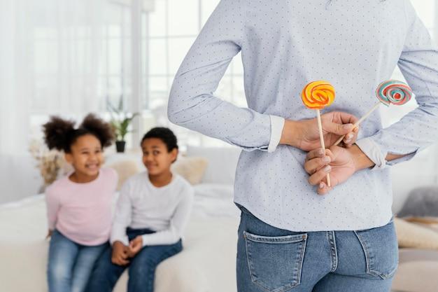 Mère cachant des sucettes à l'arrière pour ses enfants