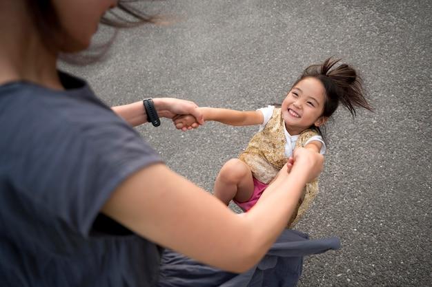 Mère célibataire jouant avec sa fille dans un parc