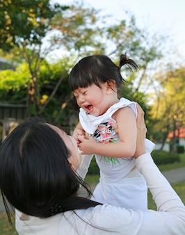 Mère close-up transportant sa petite fille et pleurer dans le parc