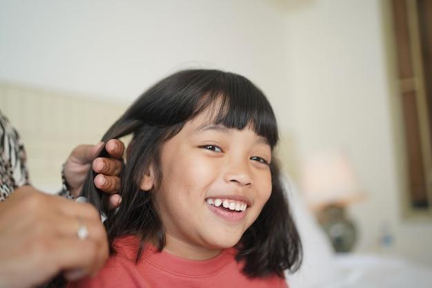 La mère coiffe les cheveux de sa fille. la femme brosse les beaux cheveux de sa fille le matin.