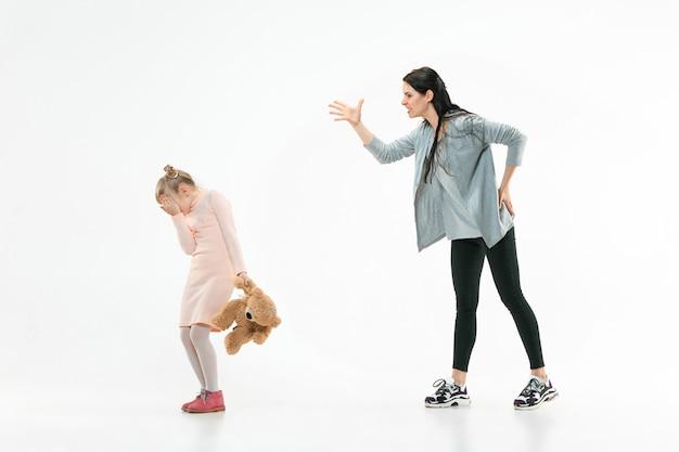 Mère en colère grondant sa fille à la maison. photo de studio de famille émotionnelle. les émotions humaines, l'enfance, les problèmes, les conflits, la vie domestique, le concept de relation