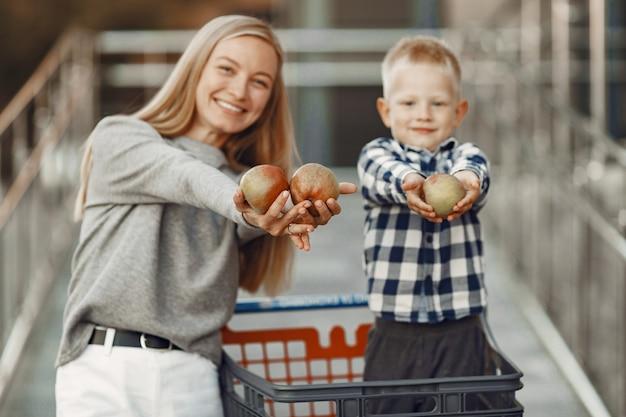 Mère conduit dans un chariot. famille dans un parking près d'un supermarché.