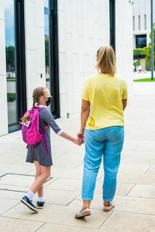 Mère conduit sa fille à étudier par la main, marcher ensemble dans le parc