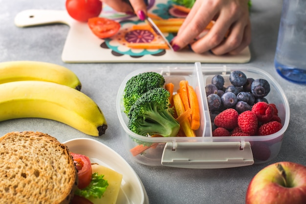 Mère coupe des légumes pour la boîte à lunch pour l'école le matin