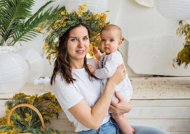 Mère avec une couronne de mimosa tient un bébé bébé dans une robe blanche sur fond de bouquets de mimosa