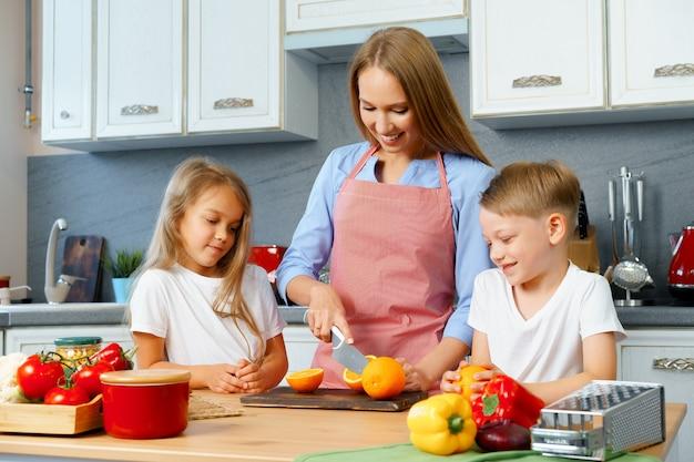Mère cuisine avec ses enfants dans la cuisine