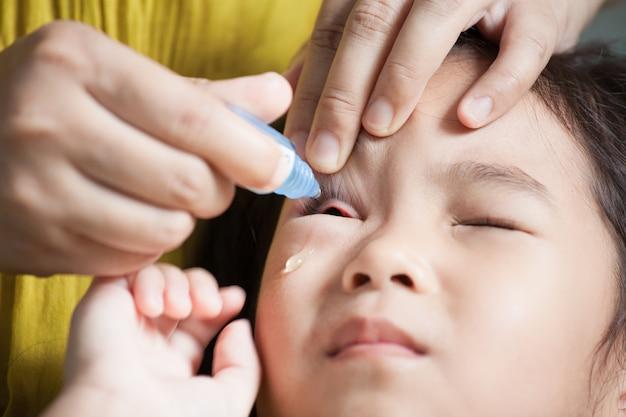 Mère dégoulinant la médecine oculaire dans les yeux de l'enfant fille