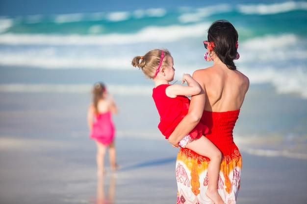 Mère et deux adorables filles marchant sur une plage exotique par une journée ensoleillée