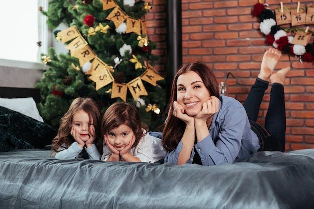 Mère et deux enfants allongés sur le lit avec une chambre décorée d'un arbre de noël.