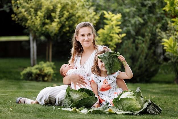 Mère et deux enfants, petite fille et petite fille sur l'herbe avec des choux le jour d'été.
