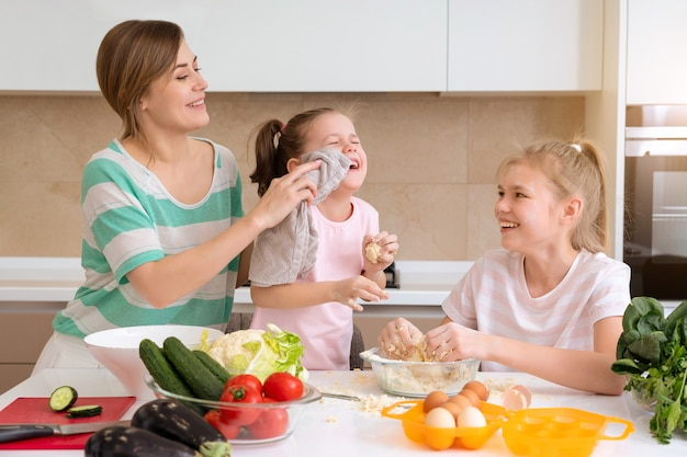 Mère et deux filles cuisinant dans la cuisine et s'amusant famille heureuse et mère célibataire