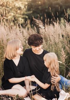 Mère avec deux filles filles dans la nature lors de la promenade estivale. maman jette ses enfants