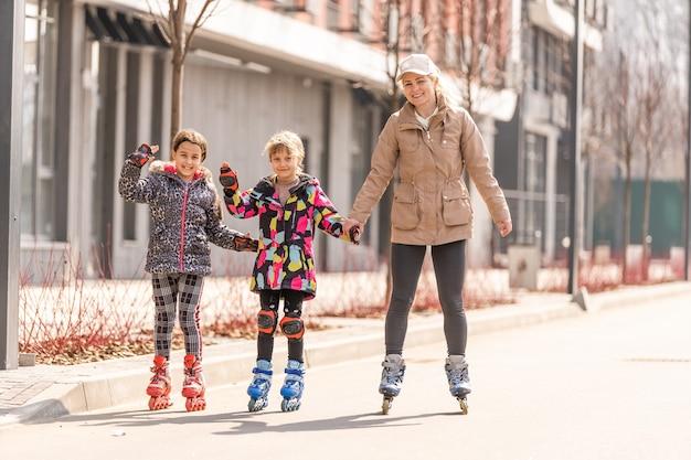 Mère de deux filles leur apprenant à faire du patin à roulettes
