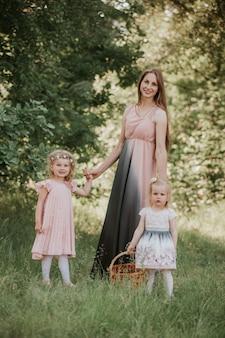 Mère et deux filles tourbillonnant. mère tient les filles sur les mains. temps en famille ensemble. un magnifique portrait de maman avec deux filles dans le parc