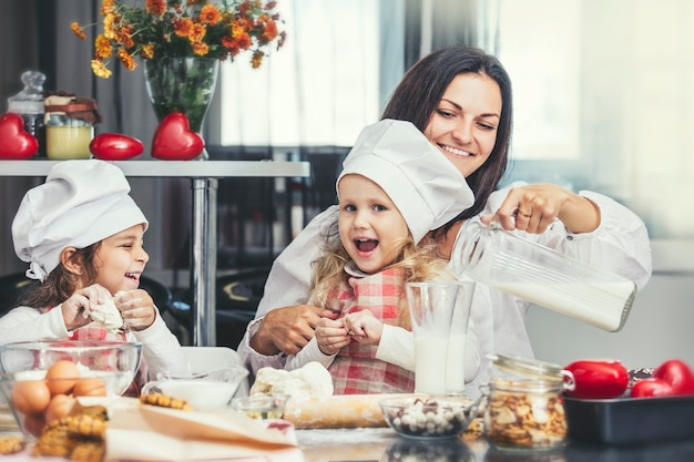 Mère et deux heureux petite fille de boire du lait et cuisiner à la table dans la cuisine est belle et belle