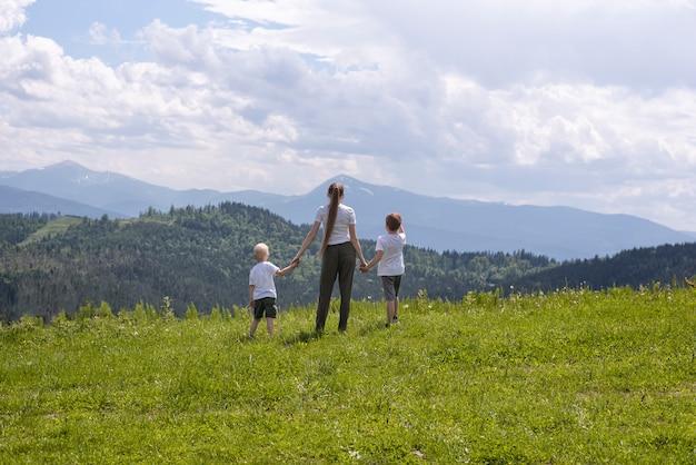 Mère et deux petits fils se tiennent la main sur un champ vert