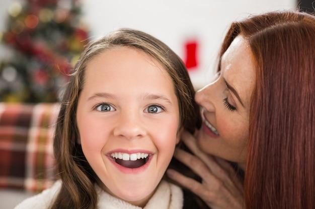 Mère disant à sa fille un secret de noël