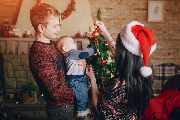 Mère distraire le bébé avec un ornement de noël tandis que le père tient dans ses bras
