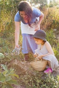 Mère donnant des gants à sa fille tenant truelle assis dans le champ