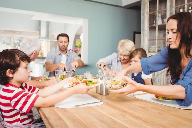 Mère donnant à manger à son fils assis à la table à manger