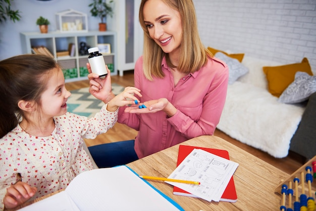 Mère donnant des pilules à sa fille tout en étudiant à la maison