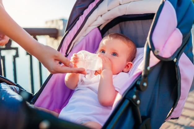 Mère donne une bouteille d'eau à sa petite fille.