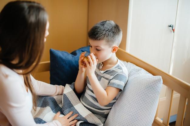 La mère donne du thé chaud au citron à son bébé pendant la maladie et le virus. médecine et soins.