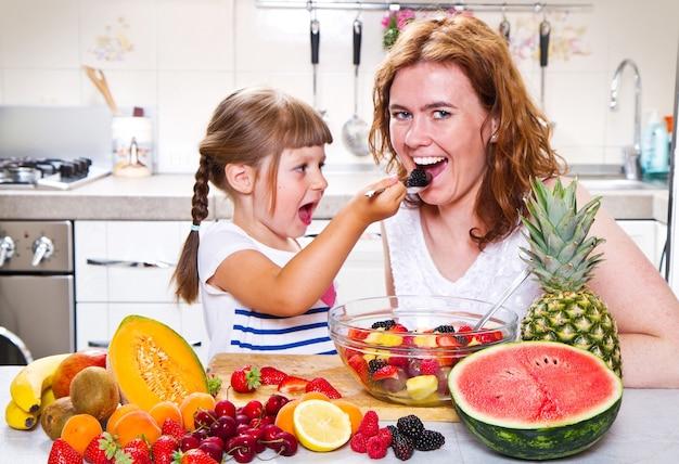 La mère donne à la petite fille une salade de fruits dans la cuisine.